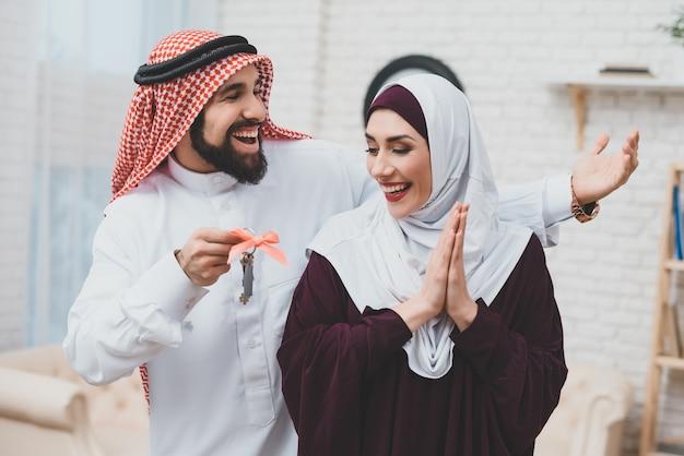 Arabischer ehemann gibt glücklicher frau neue hausschlüssel.