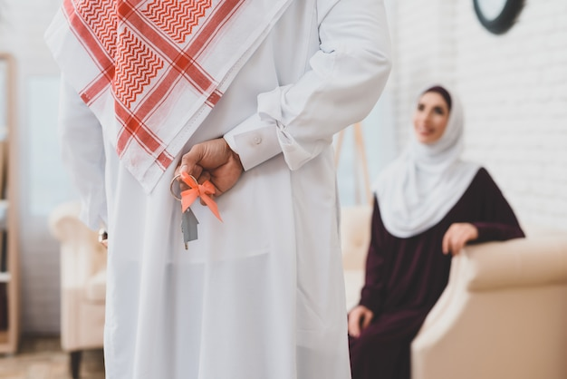Arabischer ehemann hält schlüssel hinter hinterer hypothek.