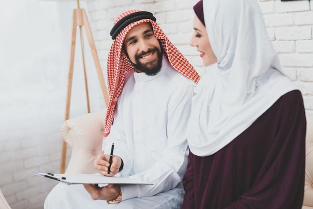 Arabischer ehemann lächelt zur frau, die vertrag unterzeichnet.