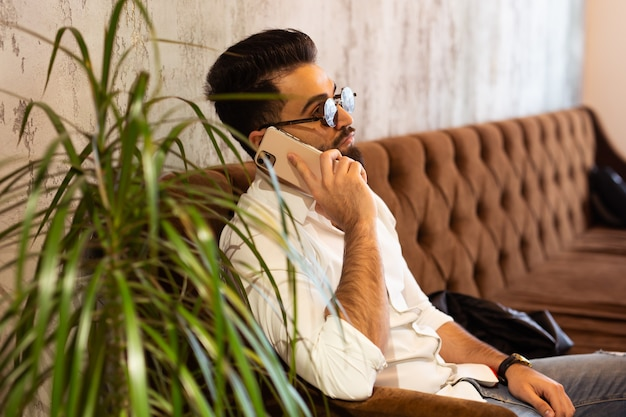 Arabischer erfolgreicher geschäftsmann oder arbeiter im weißen hemd mit bart, der mit seinem telefon in der nähe seines anruft