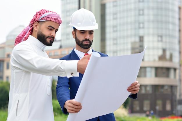 Arabischer geschäftsmann, der baupläne mit einem architekten auf einem treffen im freien bespricht