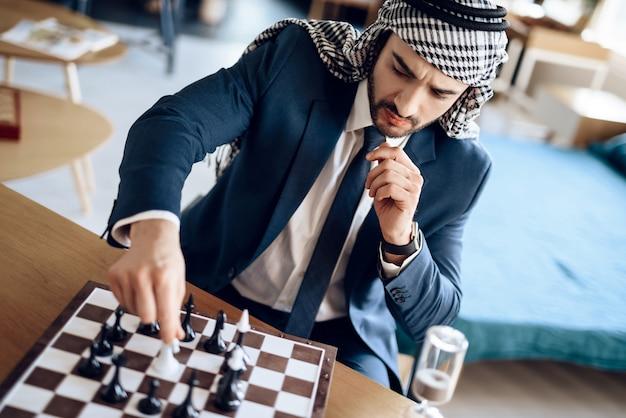 Arabischer geschäftsmann, der bei tisch schach im hotelzimmer spielt.
