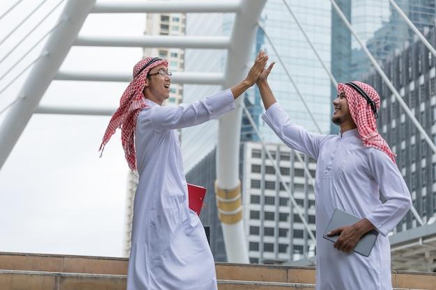 Arabischer geschäftsmann, der dem arbeitnehmer hohe fives gibt