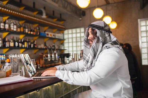 Arabischer geschäftsmann, der im büro arbeitet, geschäftszentrum, das geräte-geräte verwendet