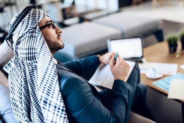 Arabischer geschäftsmann, der kenntnisse über couch am büroraum nimmt.