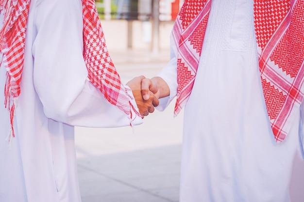 Arabischer geschäftsmann, der seinem teilhaber, auf baustelle einen händedruck gibt