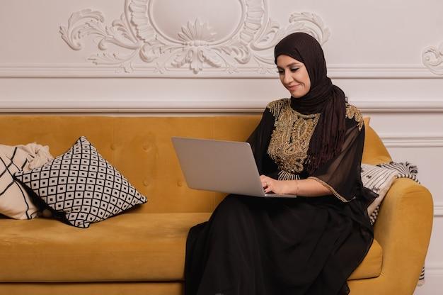 Arabischer geschäftsmann, der zu hause am laptop arbeitet. hochwertiges foto