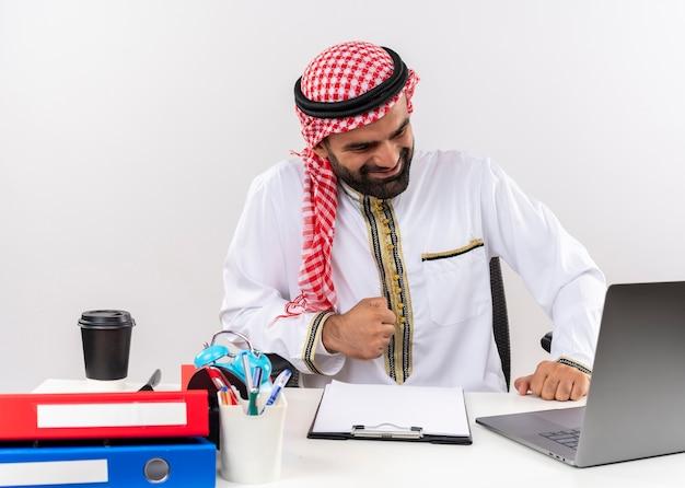 Arabischer geschäftsmann in der traditionellen abnutzung, die am tisch mit geballter faust des laptop-computers sitzt, der glücklich und aufgeregt arbeitet, im büro zu arbeiten