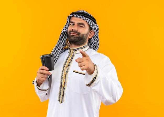 Arabischer geschäftsmann in der traditionellen abnutzung, die kaffeetasse hält, die mit dem finger zeigt, der über orange wand zwinkert und lächelt