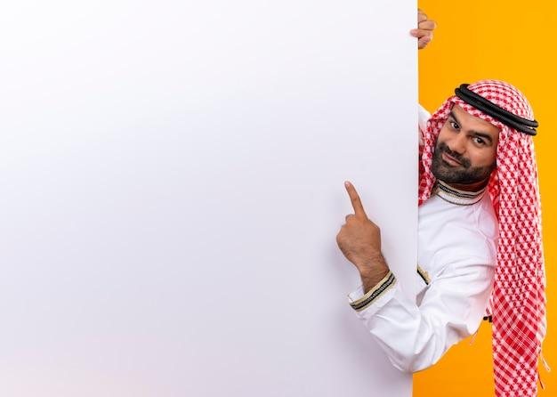 Arabischer geschäftsmann in der traditionellen abnutzung, die leere plakatwand herausspäht, die mit dem finger darauf lächelt und über orange wand steht