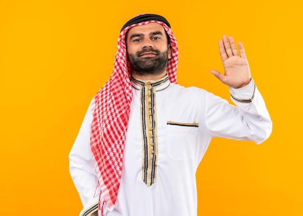 Arabischer geschäftsmann in der traditionellen abnutzung, die sicheres winken mit der hand steht über orange wand schaut