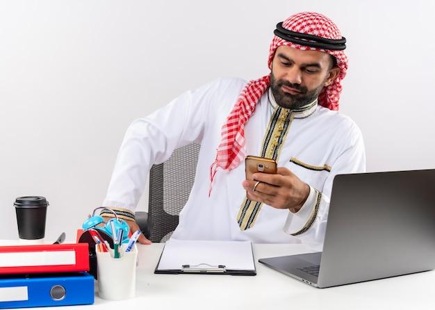 Arabischer geschäftsmann in der traditionellen abnutzungstextnachricht auf seinem smartphone, das am hellen büro arbeitet, das am tisch sitzt