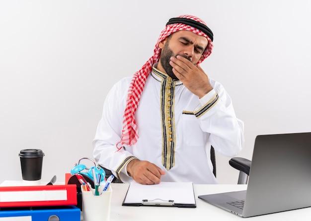 Arabischer geschäftsmann in der traditionellen kleidung, die am tisch mit laptop-computer sitzt, der müde schaut, will gähnend schlafen, das im büro arbeitet