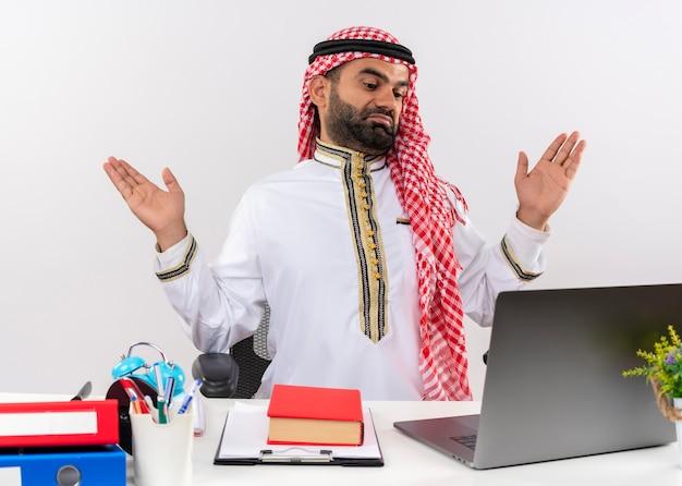 Arabischer geschäftsmann in der traditionellen kleidung, die am tisch mit laptop-computer sitzt, der verwirrt und ahnungslos sieht, die arme hebt, die keine antwort haben, die im büro arbeitet