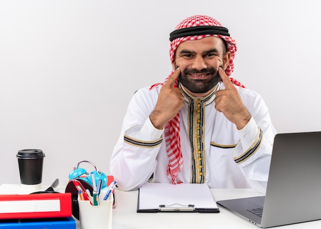 Arabischer geschäftsmann in der traditionellen kleidung, die am tisch mit laptop-computer sitzt, zeigt mit den fingern auf sein falsches lächeln des lächelns, das im büro arbeitet