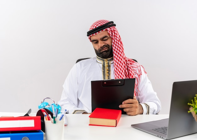 Arabischer geschäftsmann in der traditionellen kleidung, die am tisch mit zwischenablage sitzt und dokumente betrachtet, die unzufrieden arbeiten im büro