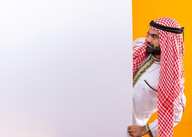 Arabischer geschäftsmann in der traditionellen kleidung, die leere plakatwand herausschaut, die es mit ernstem gesicht über orange wand betrachtet