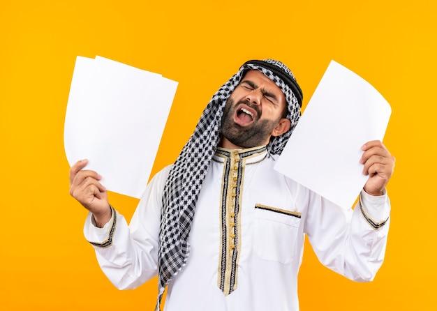 Arabischer geschäftsmann in der traditionellen kleidung, die leere seiten hält, die mit genervtem ausdruck schreien, der über orange wand steht