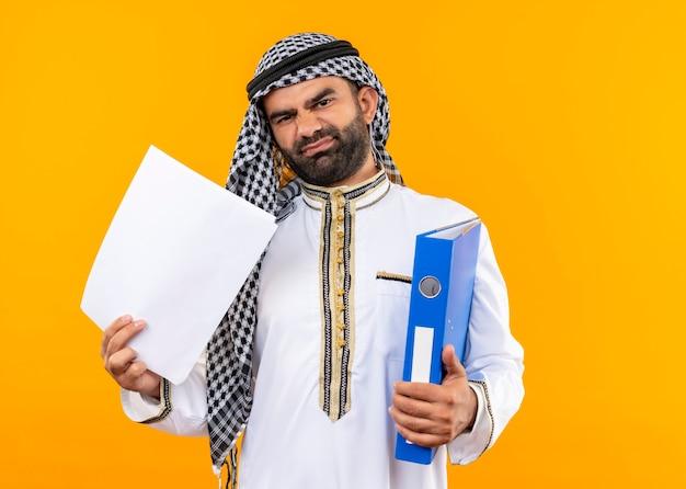 Arabischer geschäftsmann in der traditionellen kleidung, die ordner und leere seiten hält, missfiel, die über orange wand stehen