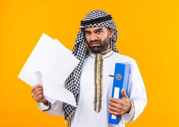 Arabischer geschäftsmann in der traditionellen kleidung, die ordner und leere seiten hält, missfiel und verwirrt, die über orange wand stehen