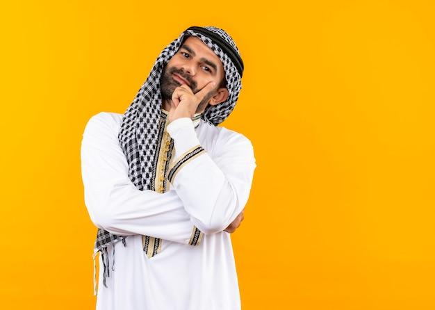 Arabischer geschäftsmann in der traditionellen kleidung glücklich und positiv lächelnd über orange wand stehend