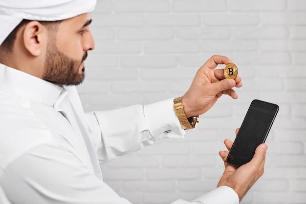 Arabischer geschäftsmann in der traditionellen weißen moslemischen abnutzung, die goldenes bitcoin und handy hält.