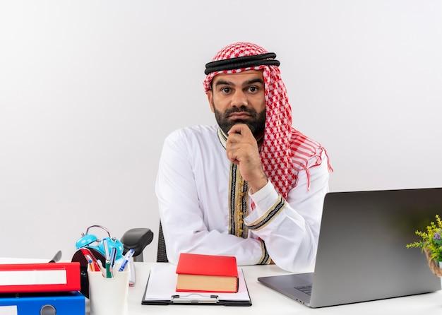 Arabischer geschäftsmann in traditioneller kleidung, die am tisch mit laptop-computer mit hand auf kinn verwirrtes denken sitzt im büro sitzt