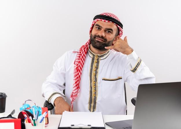 Arabischer geschäftsmann in traditioneller kleidung, die am tisch mit laptop-computer sitzt, der mich geste lächelnd im büro arbeiten lässt