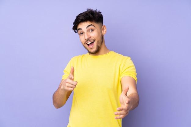 Arabischer gutaussehender mann über vereinzelt nach vorne zeigend und lächelnd