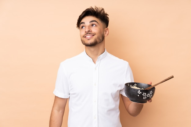 Arabischer hübscher mann auf beiger wand, die während des lächelns beim halten einer schüssel nudeln mit essstäbchen nach oben schaut