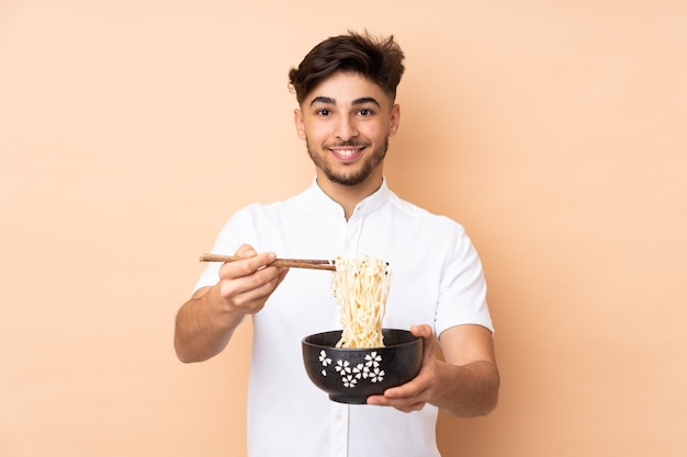 Arabischer hübscher mann lokalisiert auf beige, der eine schüssel nudeln mit stäbchen hält