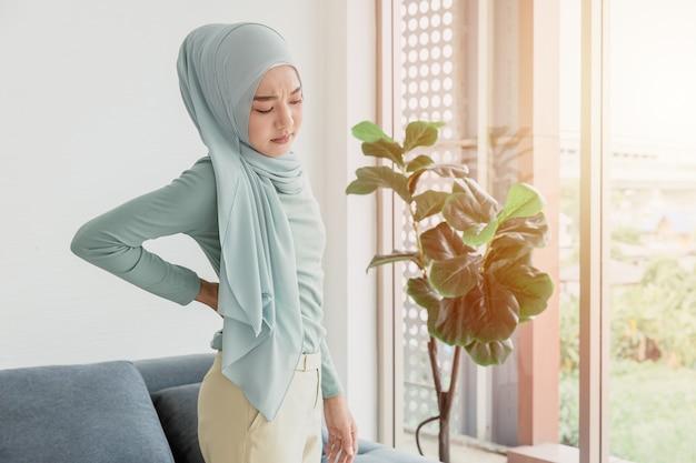 Arabischer islam frauen rückenschmerzen von büroarbeit oder nierenerkrankungen gesundheitsproblem ausdruck.