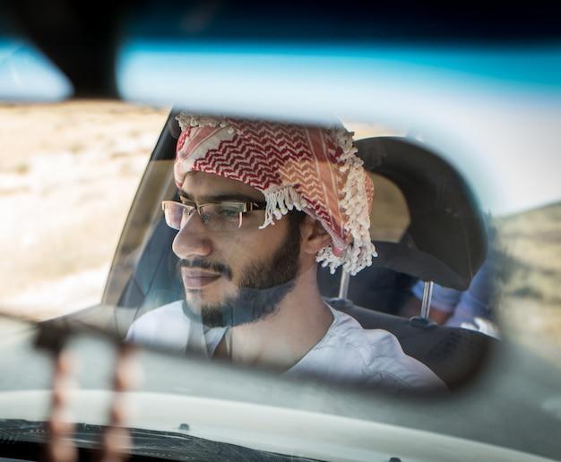 Arabischer junger mann, der auto auf straße fährt