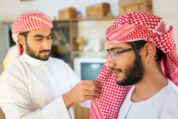 Arabischer junger mann, der kopfbedeckungen trägt