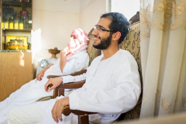 Arabischer junger mann, der zu hause auf sofa sitzt