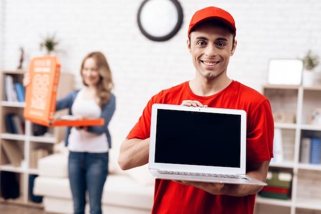 Arabischer lieferbote mit laptop und mädchen mit pizza.
