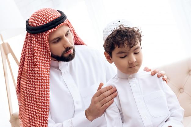 Arabischer mann bittet um vergebung von kleinen beleidigten sohn.