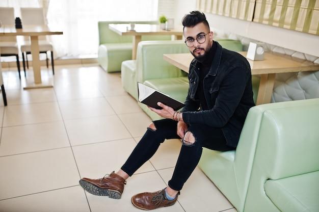 Arabischer mann, der auf schwarzen jeans und brillen sitzt, die im café sitzen und buch lesen