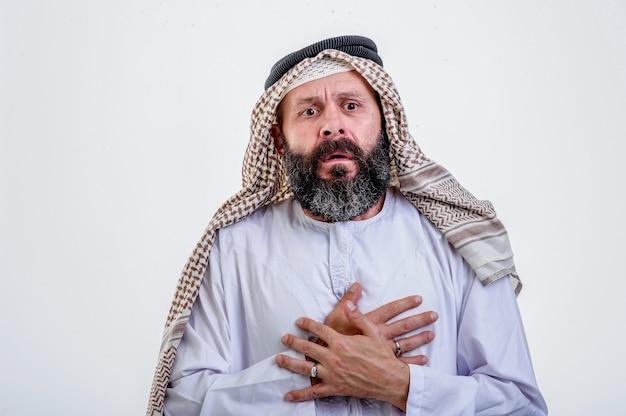 Arabischer mann, der beide hände auf die brust legt und einen herzinfarkt hat, auf weißem hintergrund.