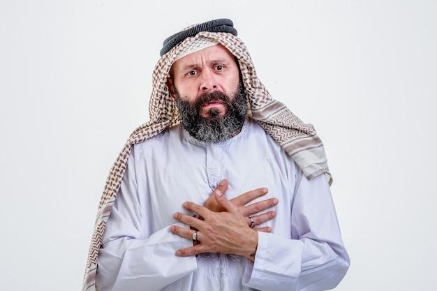 Arabischer mann, der beide hände auf die brust legt und herzinfarkt hat, auf weißem hintergrund.