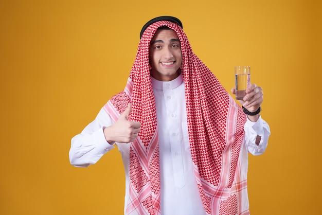Arabischer mann, der sich daumen zeigt und ein glas wasser hält