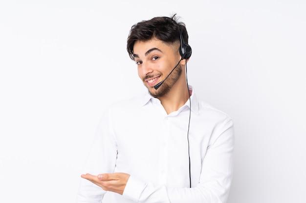 Arabischer mann des telemarketers, der mit einem auf weißer wand isoliertes headset arbeitet, das hände zur seite ausdehnt, um einzuladen, zu kommen