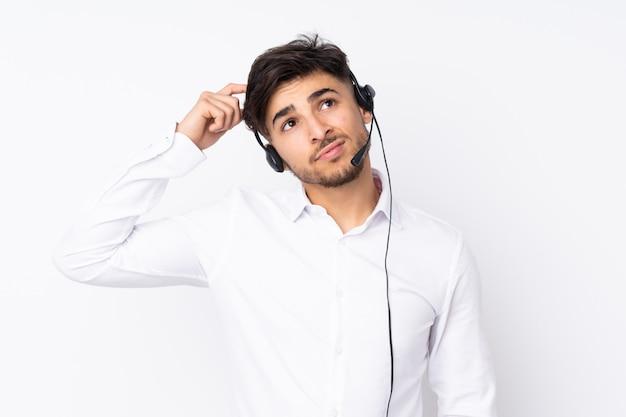 Arabischer mann des telemarketers, der mit einem headset an der weißen wand arbeitet, die zweifel und mit verwirrtem gesichtsausdruck hat