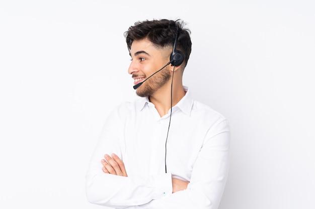 Arabischer mann des telemarketers, der mit einem headset arbeitet, das auf weiß lokalisiert wird, das zur seite schaut