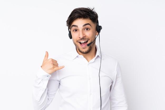 Arabischer mann des telemarketers, der mit einem headset arbeitet, das auf weiß lokalisiert wird und telefongeste macht