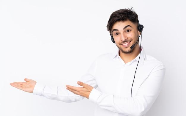 Arabischer mann des telemarketers, der mit einem headset arbeitet, das auf weißen ausgestreckten händen zur seite für einladung zum kommen isoliert wird