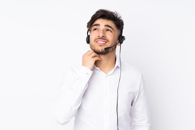 Arabischer mann des telemarketers, der mit einem headset arbeitet, das auf weißer wand lokalisiert wird, die eine idee denkt