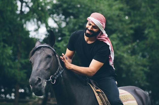 Arabischer mann in der schwarzen kleidung, die auf einem pferd sitzt
