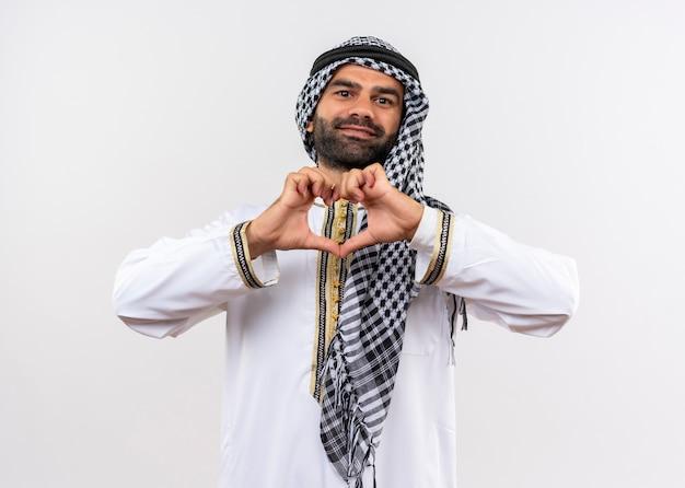 Arabischer mann in der traditionellen abnutzung, die herzgeste mit den fingern macht, die glücklich und positiv lächelnd über weißer wand lächeln
