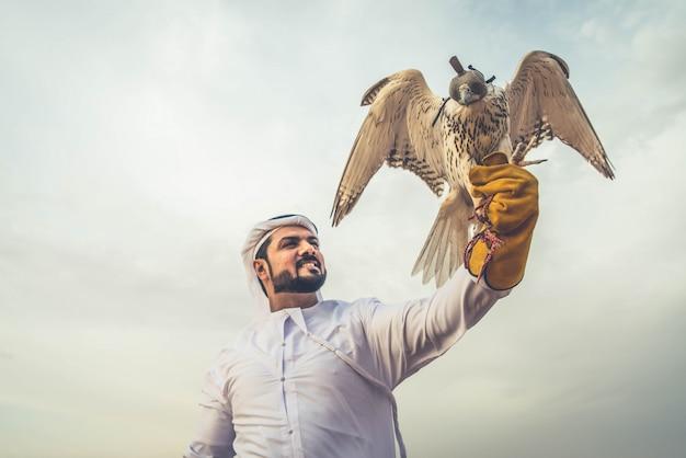 Arabischer mann in der wüste mit seinem falken